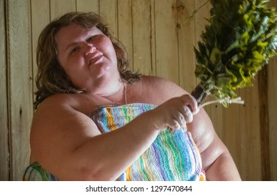 Russian woman in a bathhouse with a broom steamed