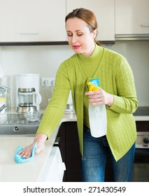 russian woman cleaning  furniture in kitchen