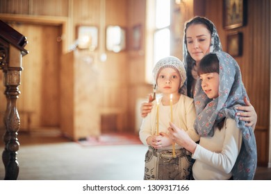 Russian woman praying in front of icons on her knees with her little daughters in the Orthodox Church
