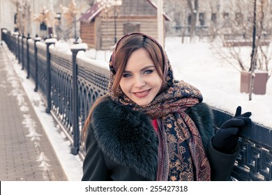Russian woman in winter weared in traditional shawl near fence, toned image