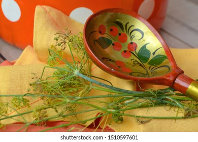 Russian wooden khokhloma spoon on orange napkin with fresh dill, russian style. A wooden spoon painted in Khokhloma style - a traditional ancient Russian handicraft