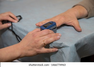 Russia,Saint-Petersburg. 21 March 2019. Doctor using pulse oximeter to examine patient. Senior patients are being measures the amount of oxygen in the blood and the rhythm of the heart