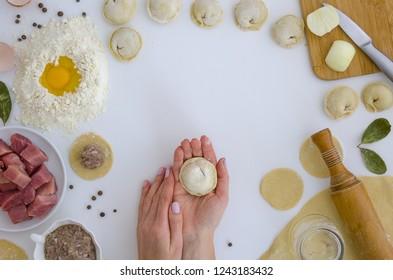 Russiat food. Home-made recipe for dumplings ravioli. Traditionally, woman hold the dumplings in the family. Flat lat frame mock up. hero header pelmeni