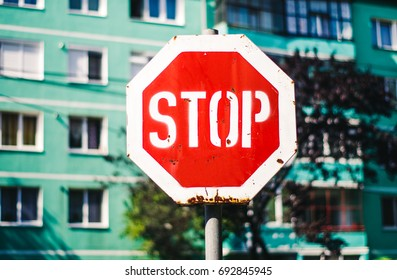 Rust stop sign in front of flat building