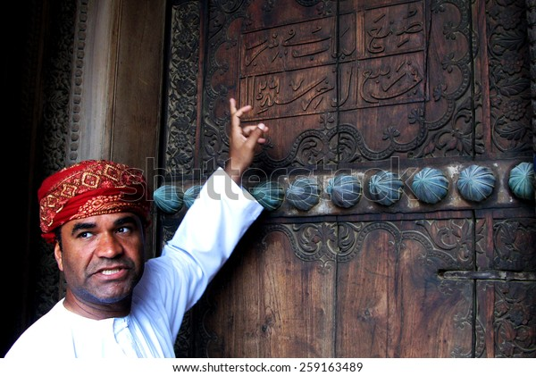 RUSTAQ, OMAN - DEC 23 2007:Omani tour guide explain the meaning of Arab words on the gate of Al Hazm Fort.Arabic is a Semitic language, date back to AD 512-568 closely related to Aramaic and Hebrew.
