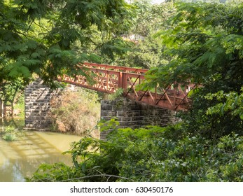 Rusted and abandoned iron bridge between the trees
