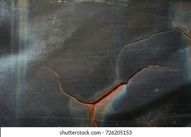 Rusted black painted metal wall. Rusty metal background with streaks of rust. Rust stains. The metal surface rusted spots