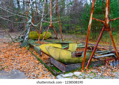 Rusted boat swings at amusement park in abandoned ghost town of Pripyat, Chernobyl NPP alienation zone, Ukraine