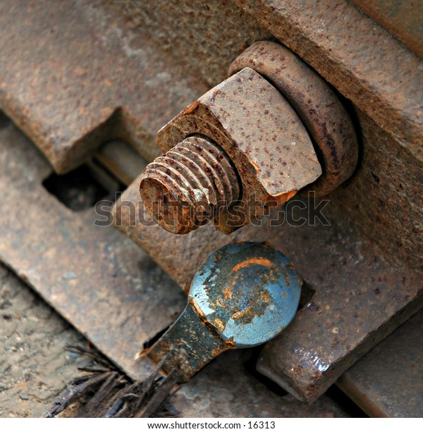 Rusted bolt and screw with nail of train tracks