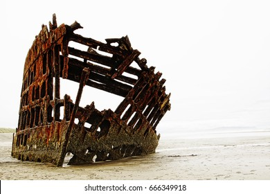 The rusted frame of the Peter Iredale rests wrecked in heavy fog on the northwest Oregon coast.  The sailing vessel was a four-masted steel barque that ran aground in 1906 and is now a tourist spot.