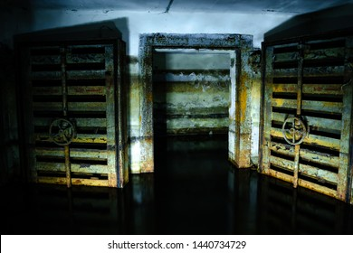 Rusted hermetic metal doors in flooded abandoned Soviet time fallout shelter. Illuminated by flashlight.