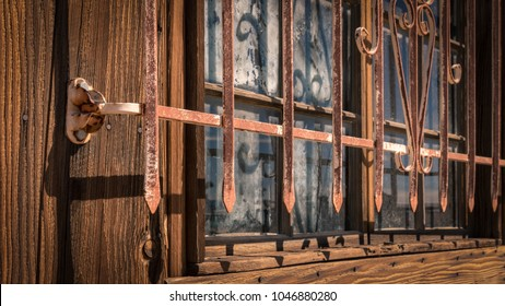 Rusted iron bars protecting window set in weathered wooden wall