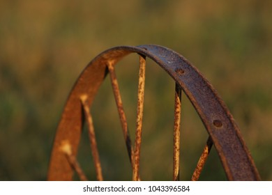 Rusted iron wheel with spokes against green background. brown used up rust on wheel