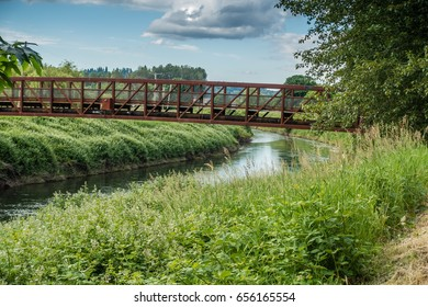 A rusted metal bridge spans the Green River in Kent, Washington.