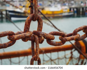 Rusted metal chains of the fishing nets of a fishing trawler boat moored in Newlyn harbour. Cornwall, England.