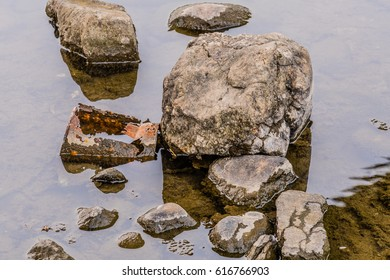 Rusted metal container in river among rocks and stones