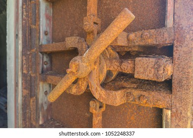 Rusted metal door with deadbolt lock in an old abandoned fortification construction on a bright summer day on Vallisaari island in Finland