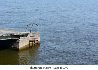 Rusted metal ladder on the side of a jetty, reaching down into water - with copy space