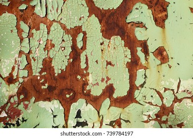 Rusted metal plate - sheet metal with cracked and peeled layer of green paint; background; texture; pattern; copy space; sign board