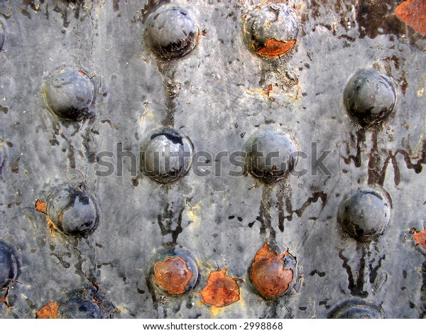 rusted metal rivets on the side of an old granary - horizontal view