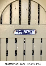 """rusted metal sign on wood plank door saying """"Tradesmen's Entrance"""""""