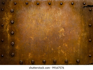 Rusted metal wall plate with three borders of metal studs, showing orange and brown scratch and scuff marks.  Suitable for wallpaper or background or grunge texture.