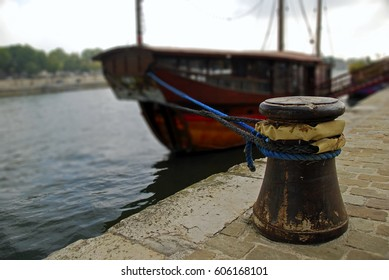 Rusted mooring bollard with ropes on the berth. Moored tourist boat in the blurred background. River Seine, Paris, France