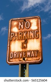 """Rusted """"No Parking in Driveway"""" sign with blue sky in background."""