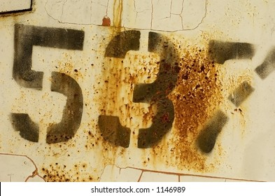 A rusted number stamp on a metal trailer.