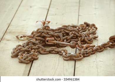 Rusted old chain links with hook on wooden planked dock