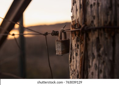 A rusted padlock hangs on a weathered wired fence of a Midwest farm.
