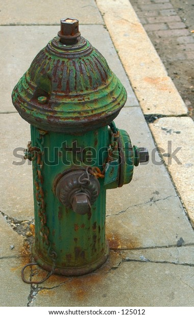 Rusted, paint peeling and uniquely colored green fire hydrant located in Southwest Washington, DC.