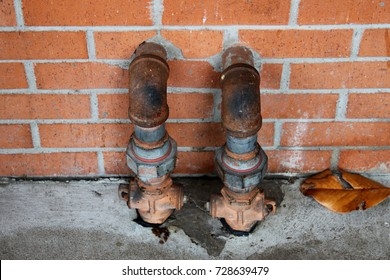 Rusted Pipes Coming Out of a Brick Wall