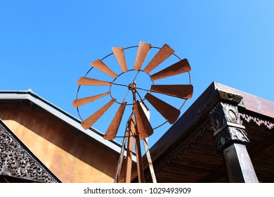 Rusted rustic windmill etched against blue sky, with ornate frames in background