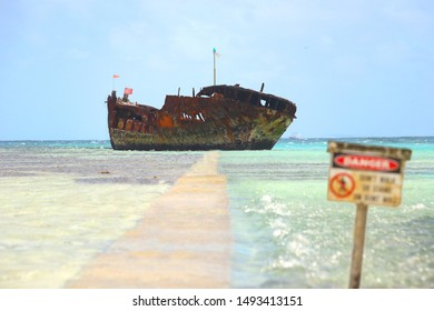 """A rusted shipwreck exposed in shallow water, with a """"danger"""" sign on foreground"""