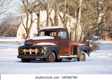 Rusted vintage 1950s truck in a white winter landscape