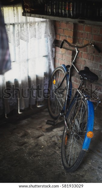 Rusted Vintage Bike leaning against a stone wall in garage