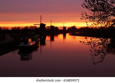RUSTENBURG, THE NETHERLANDS - APRIL 1, 2017: A view over a canal on three old Dutch windmills at sunset.