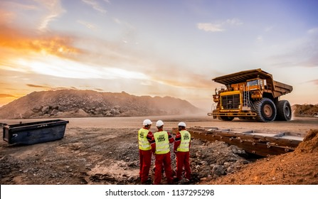 Rustenburg, South Africa, October 15, 2012, Large Dump Trucks transporting Platinum ore for processing with mining safety inspectors in the foreground
