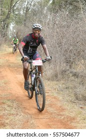 Rustenburg, South Africa - OCTOBER 23, 2016: Middle aged Black African man enjoying outdoors ride at Mathaithai Mountain Bike Race, Rustenburg, South Africa.
