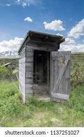 Rustic Alaskan outhouse in summer on a sunny day.