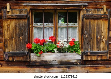 rustic and alpine wooden window with flowers