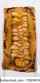 Rustic apple tart baked in puff pastry with a sweet apricot glaze