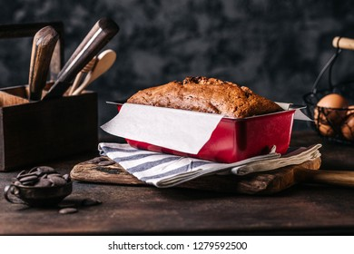 Rustic arrangement of baked bread loaf in metal form on wooden table with utensil around