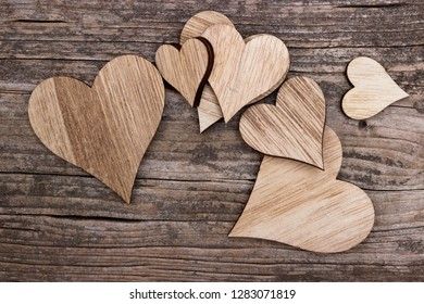 Rustic assortment of different wooden hearts on a wooden plate