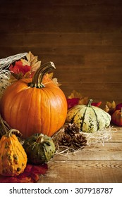 A rustic autumn still life with pumpkins and a Jack O'Lantern on a wooden table.