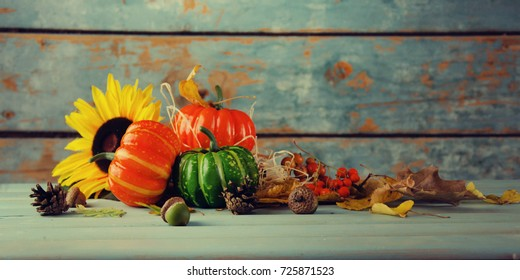 A rustic autumn still life with pumpkins and golden leaves on a wooden surface.Thanksgiving day concept.