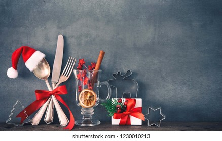 Rustic background for Christmas dinner with cuttlery, gift box and Santas hat