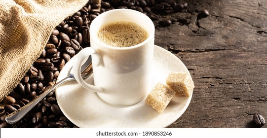 Rustic background with cup of coffee espresso in white porcelain cup with roasted coffee beans on old wood background with canvas bag. Morning cup of coffee concept