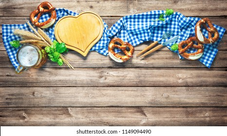 Rustic background for Oktoberfest or Bavarian specialties with white and blue fabric, hop, silverware, beer glass and pretzels on wooden table. Menu card for Restaurants